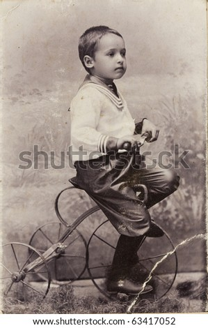 A little boy on a bicycle, old photo