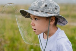 A little boy on the field is looking closely at a spider's web at sunrise in the fog. Young naturalist. Observation of the nature of the child