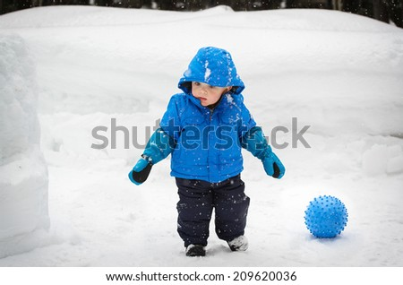 A little boy outside in the snow in the winter time with a ball on the ground next to him.