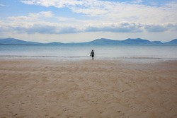 A Little Boy Playing on Newborough Beach near LLandwyn Island (Ynys Llandwyn) in Anglesey, Gwynedd, Wales, UK. Snowdonia Mountains in the Background.