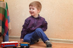 A little boy playing with a railroad sitting on the floor