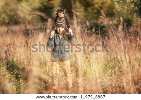 A little boy plays funny games with his monkey toy in the forest
