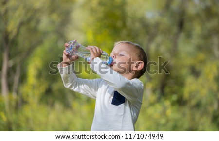 A little boy quenches his thirst with a bottle of still water on a halt in the forest on a sunny day