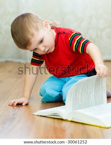a little boy reads a book