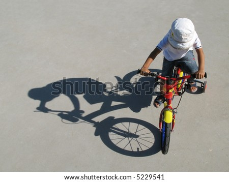 A little boy riding a bike with his shadow on a gray background