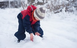 A little boy rolls handles ball of snow. Games with the snow. Baby in bright jumpsuit and wool cap