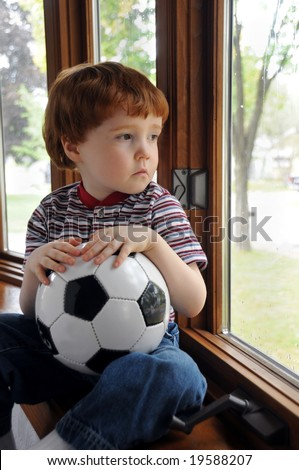 A little boy sits by a window on a rainy day, wishing he could go outside and play soccer