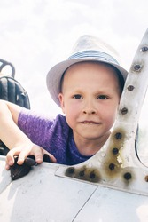 A little boy sits in the cockpit of an old military plane. Rusty metal supports and rivets are visible.