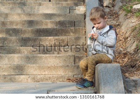 A little boy sits intently on the street and waits.