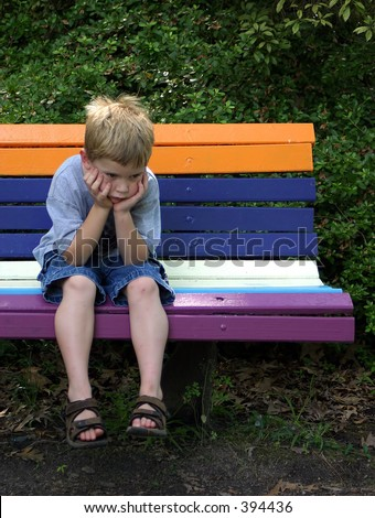 A little boy sitting on a park bench waiting and looking bored.