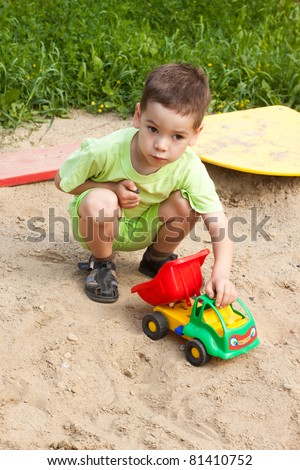 a little boy smiling and playing in the toy car in the children'