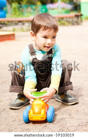 a little boy smiling and playing in the toy car in the children's village on a summer day