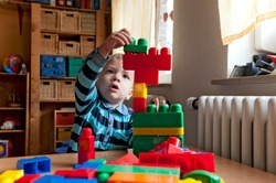 A little boy stacking building blocks on a table.