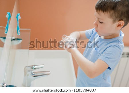A little boy washes his hands with soap in the bathroom. The concept of cleanliness and hygiene.