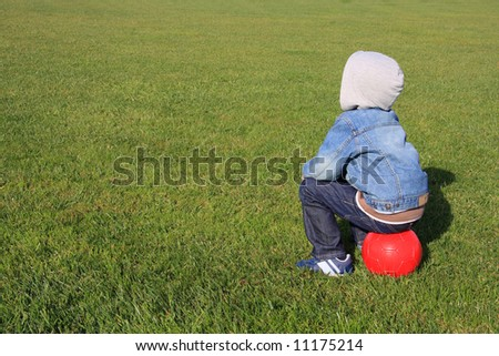 A little boy with a red ball on a green field with copy-space for text