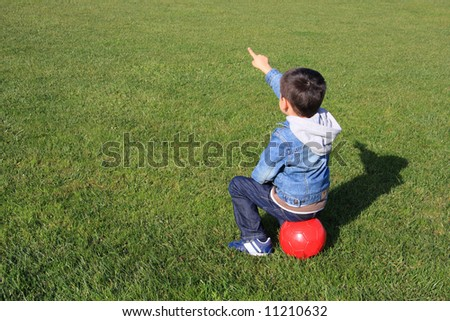 A little boy with a red ball sitting on the gass