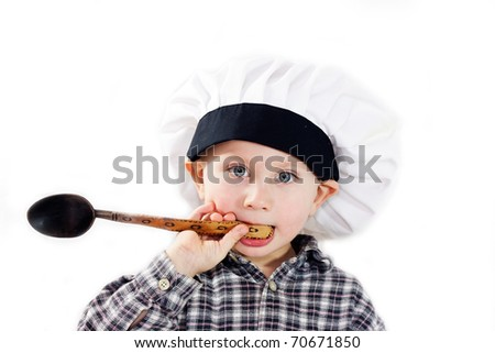 A little boy with a spoon and a hat cook isolated on white background