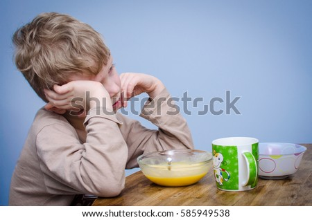 A little boy with curly blond hair, a beige t-shirt sitting at a table at lunch in front of him a plate of food puree soup porridge. A spoiled child do not want to eat and covers his face with hands. #585949538