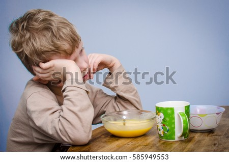 A little boy with curly blond hair, a beige t-shirt sitting at a table at lunch in front of him a plate of food puree soup porridge. A spoiled child do not want to eat and covers his face with hands. #585949553