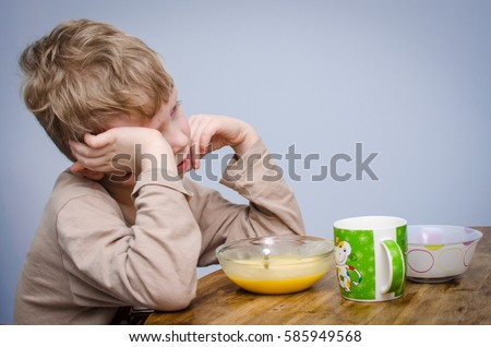A little boy with curly blond hair, a beige t-shirt sitting at a table at lunch in front of him a plate of food puree soup porridge. A spoiled child do not want to eat and covers his face with hands. #585949568