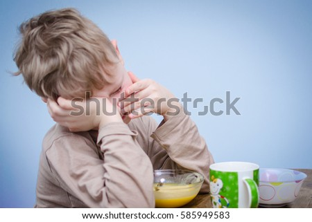 A little boy with curly blond hair, a beige t-shirt sitting at a table at lunch in front of him a plate of food puree soup porridge. A spoiled child do not want to eat and covers his face with hands. #585949583