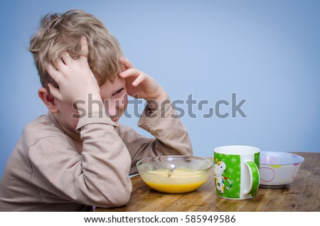 A little boy with curly blond hair, a beige t-shirt sitting at a table at lunch in front of him a plate of food puree soup porridge. A spoiled child do not want to eat and covers his face with hands. #585949586