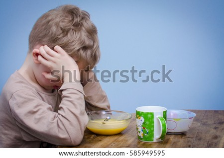 A little boy with curly blond hair, a beige t-shirt sitting at a table at lunch in front of him a plate of food puree soup porridge. A spoiled child do not want to eat and covers his face with hands. #585949595