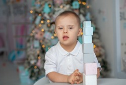 A little boy with Down syndrome builds a tower of blocks, a child with a genetic disease, disabled children celebrate the New Year, Christmas tree lights around the baby, New Year's mood.