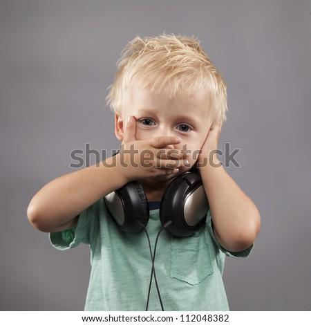 A LIttle Boy with headphones holds hands over ears and mouth.