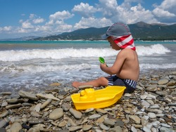 A little boy with panama hat plays on the beach by the sea. He holds in his hands a yellow toy ship and green shoulder blade