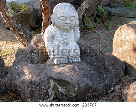 A little Buddhist rock statue in a Japanese rock garden