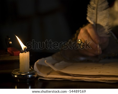 A little candlelit detail image showin a blurred hand writing a manuscript with quill in the background