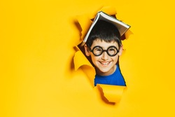 A little cheerful nerd boy in black glasses and an open book on his head break through a yellow colored paper wall. Sidebar for advertisements, events. Back to school and good luck.