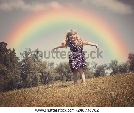 A little child is dancing in an open grass field with wind blowing in her hair and a rainbow in the background for a freedom or spring concept.