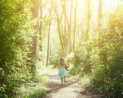 A little child is running down a nature trail with sunlight on the trees for a happiness or freedom concept.