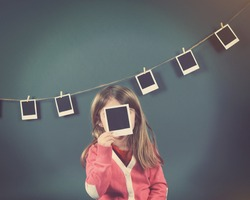 A little child photographer is holding up a photo of a blank film print and other photos on the wall for a art or creativity concept.