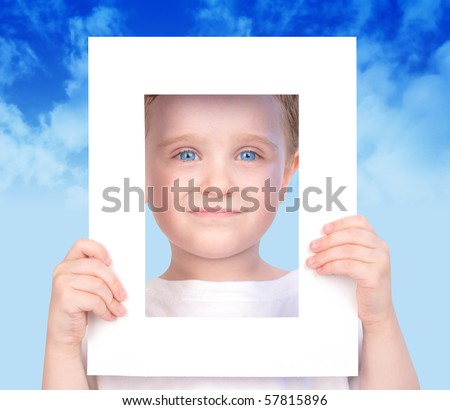A little cut boy is holding a white frame and his face is looking through it. There are clouds in the background and he has blue eyes. Use it for a future or imagination concept.