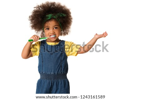 A little cute african american girl brushing her teeth, isolated over white background. Healthy teeth concept. Foto d'archivio ©