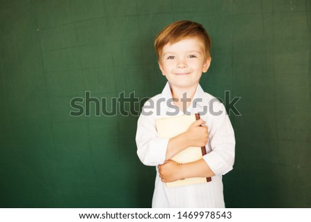 A little cute and a little sad boy stands on the background of the school board with a book in his hands