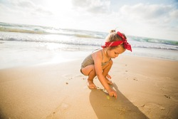 A little cute baby girl is playing on a beach near a sea.