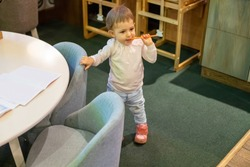 a little cute baby girl is standing with a pencil in his mouth at the children's small low table and child seats in the children's area. on the table are pencils and books. top view, soft focus