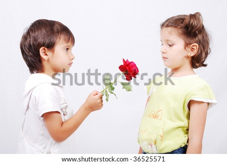 A little cute boy is offering a rose to little girl