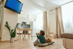 A little cute girl holding a gamepad playing videogames on a TV while sitting on a floor cross-legged in a middle of a spacy room being alone at home. Childrens leisure activities