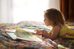 A little cute girl in a yellow dress reading a book lying on the bed