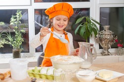 A little cute girl in an orange cap and apron prepares dough from flour, eggs and milk, a child mixes ingredients in a glass bowl, a little cook prepares food in the kitchen.