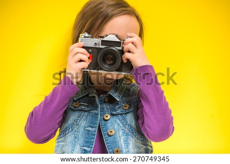 A little cute girl making photo on yellow background.
