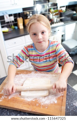 A little cute happy girl is cooking the dough for making biscuits in the kitchen