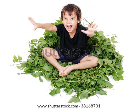 A little cute kid sitting on green leaves chair