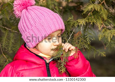 A little cute little girl in a pink jacket looks out by nature in a park near a tree
