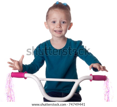 A little dare devil attempts to ride her bike without any hands.